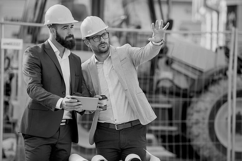 male construction worker with hardhat and coffee showing jobsite to his partner