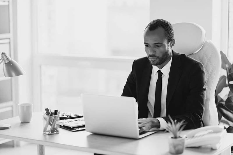 Businessman sitting at his desk using laptop