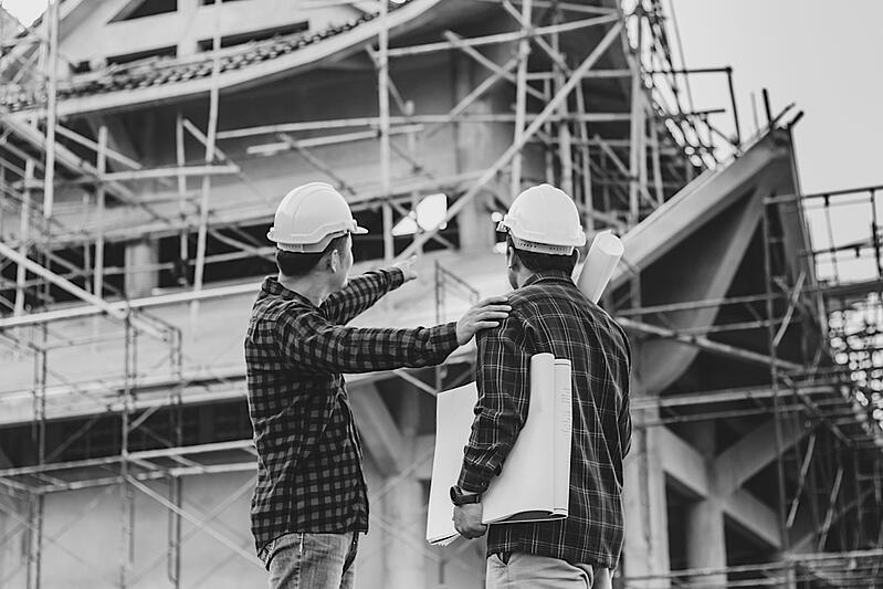 two construction workers observing construction jobsite