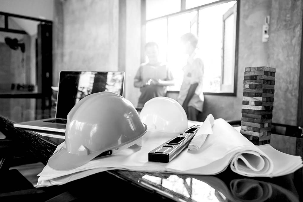 construction hard hat, laptop, and building blocks resting on a desk