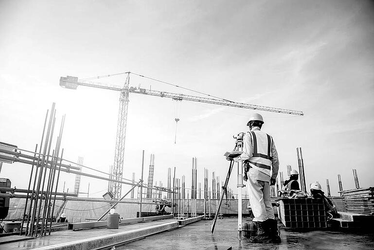 construction worker with hardhat filming at construction site with camera tripod