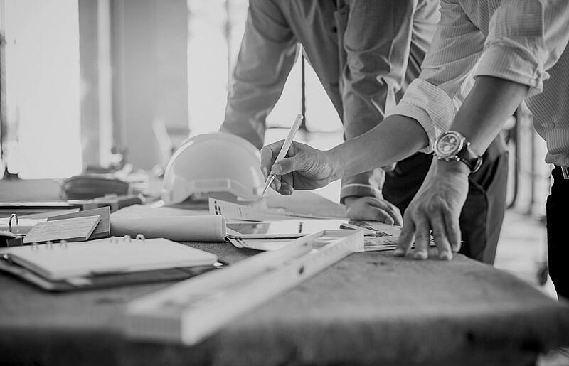 contractors at desk assessing construction plans with pencil, ruler, and hardhat