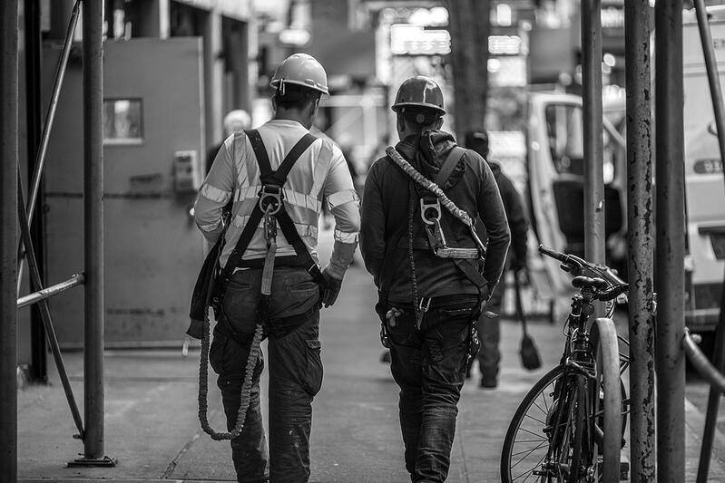 two construction workers with hardhats walking through the city