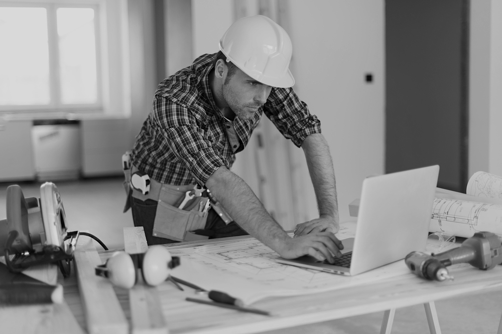 construction worker with hardhat using laptop on desk with construction tools