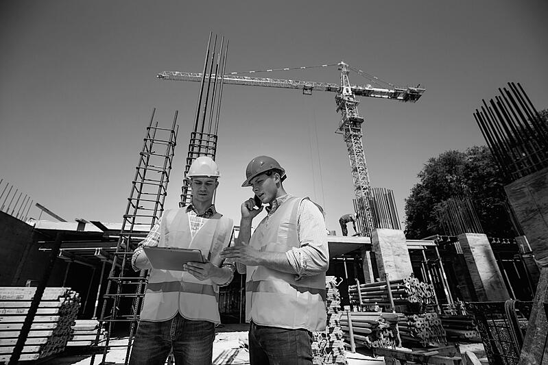 two construction workers with hardhats discussing plans in front of jobsite