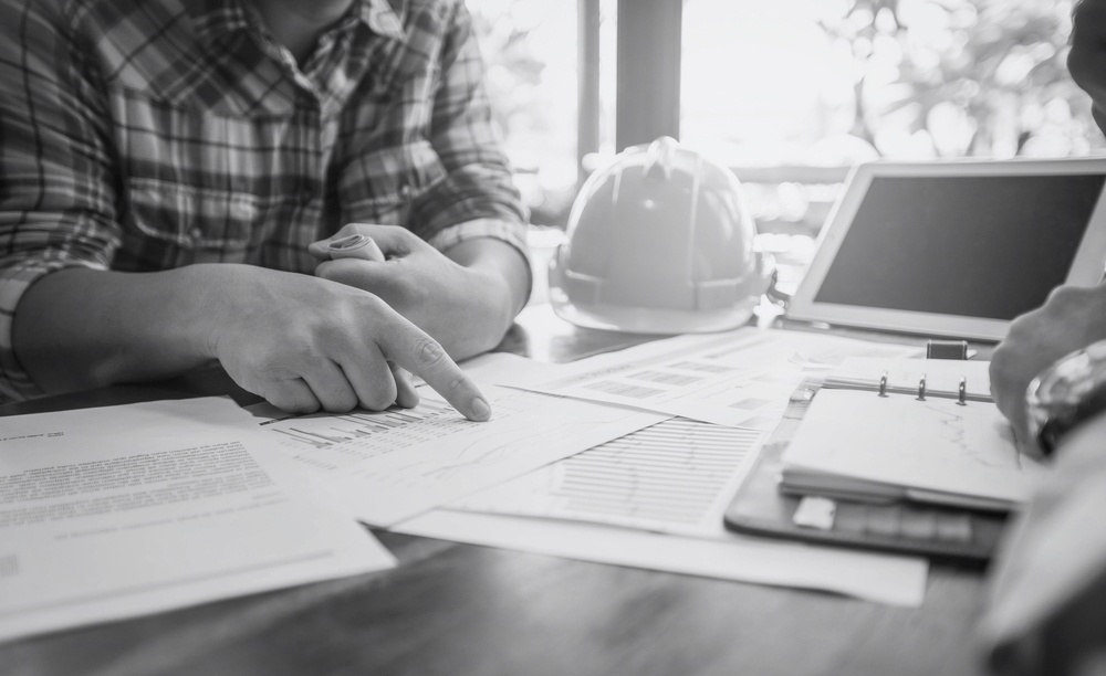 contractor sitting at desk and pointing at insurance papers