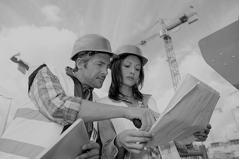 male construction worker showing worksite plans to female construction worker wearing hardhat