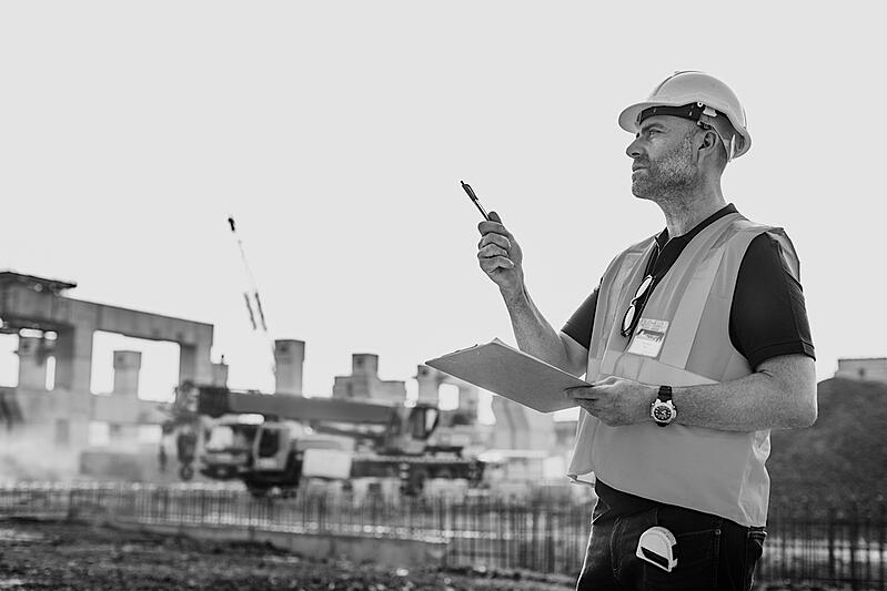 construction worker outside with clipboard and pen evaluating work site