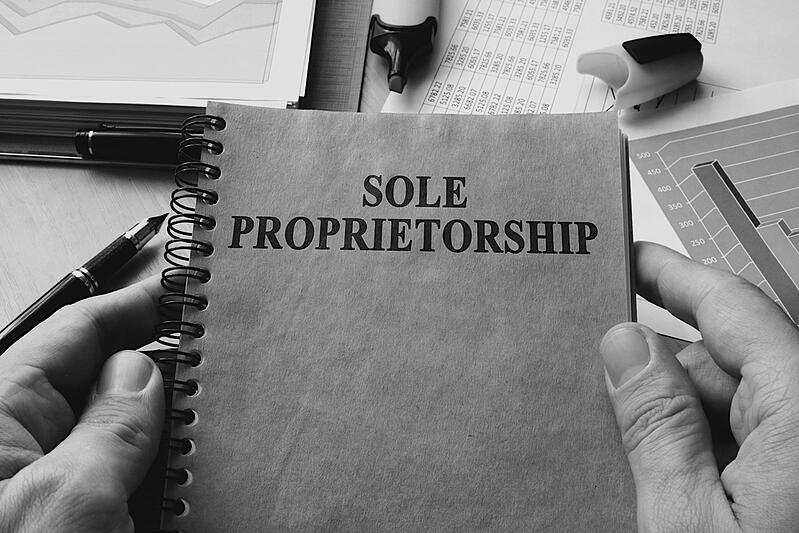 person in front of cluttered desk holding notebook with sole proprietorship