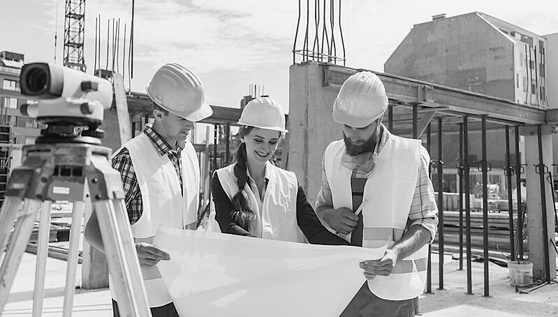 female construction worker showing jobsite plans to two male workers at construction site
