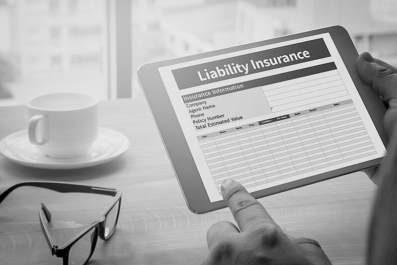 person holding tablet and reviewing liability insurance information