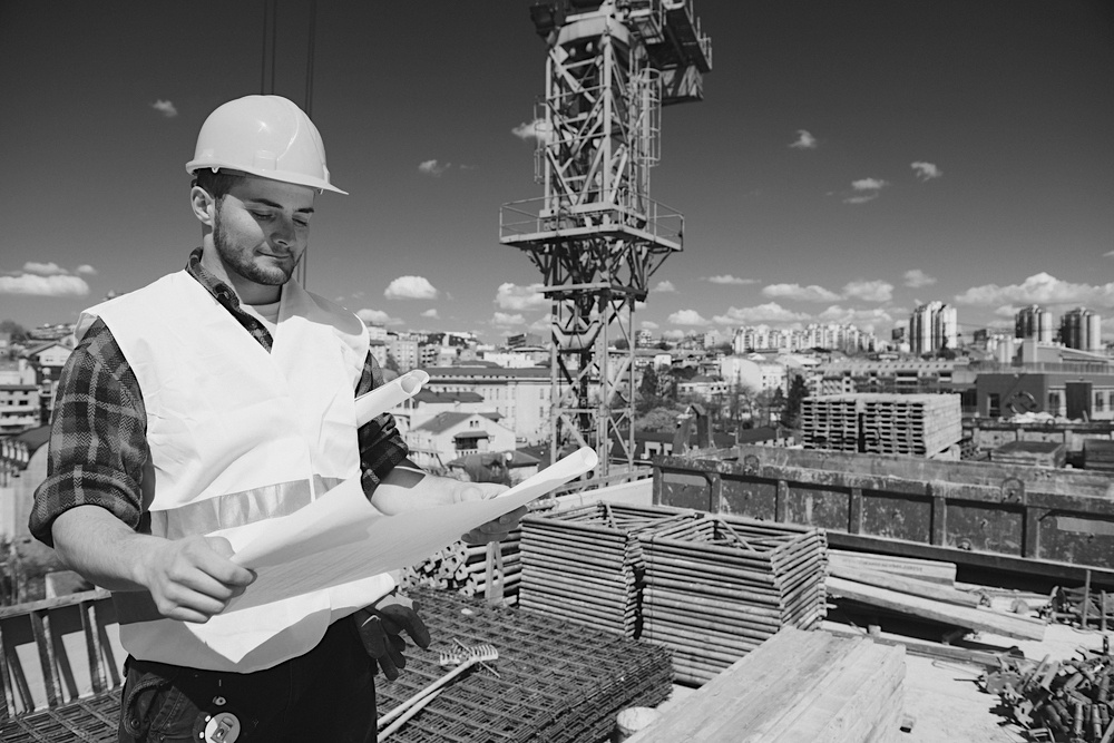 male construction worker with hardhat and uniform reviewing construction plans at jobsite