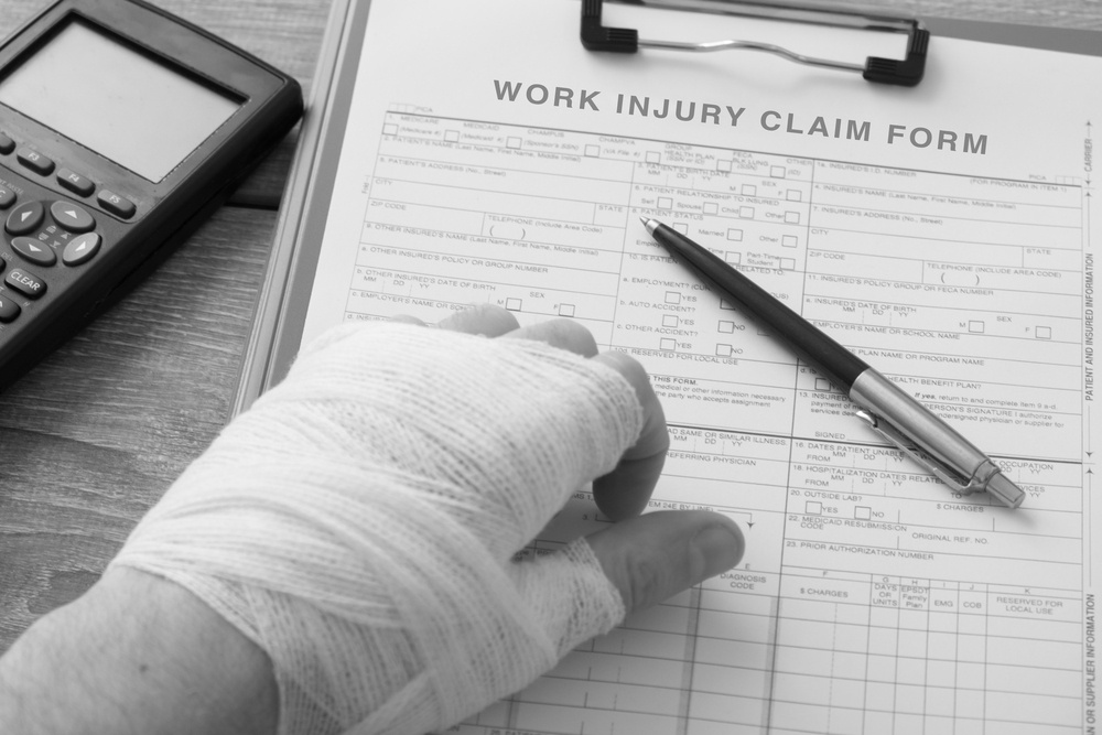 injured hand with bandages resting on desk with work injury claim form