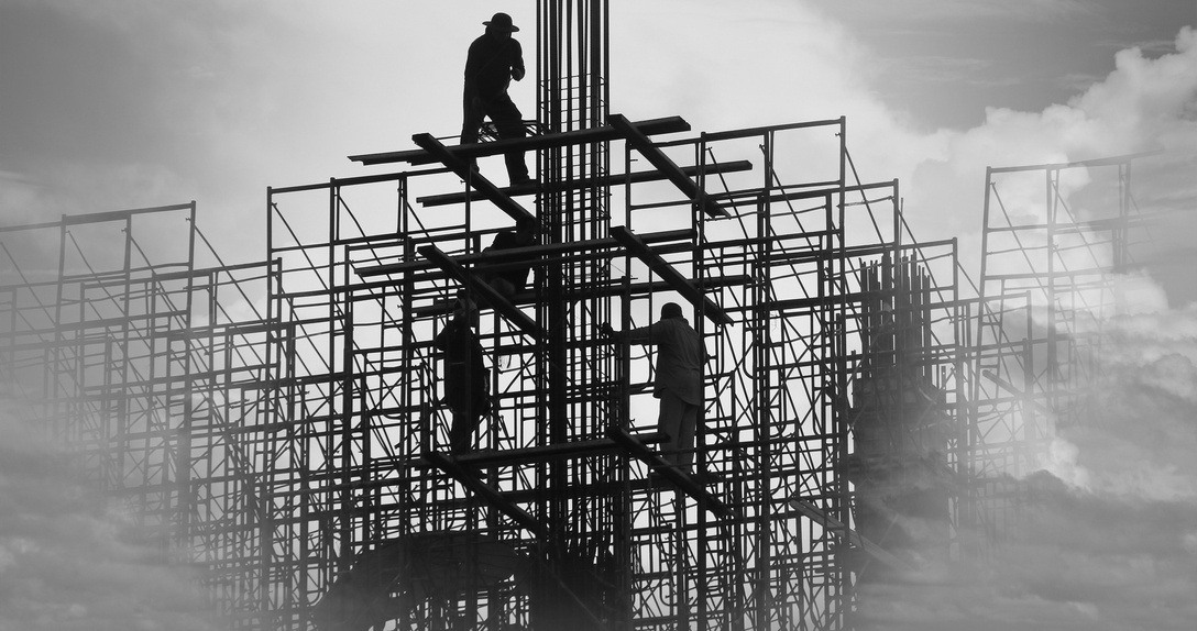 silhouette of construction workers on steel beams at jobsite