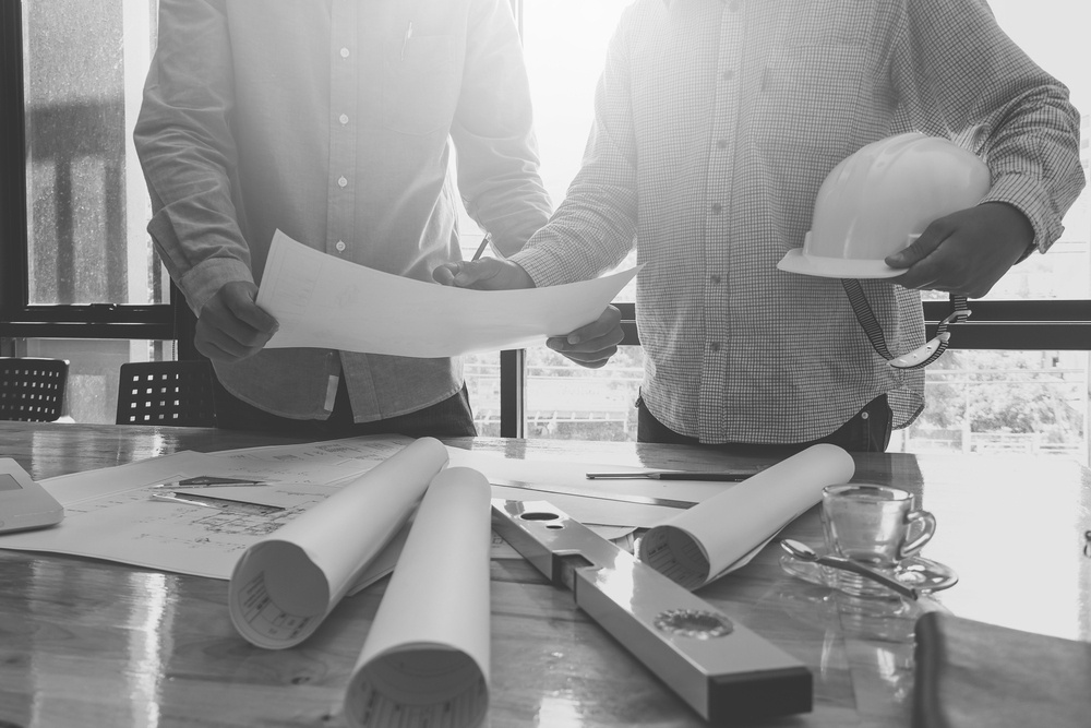 two construction workers reviewing job site plans in front of table with hardhat and drafting equipment