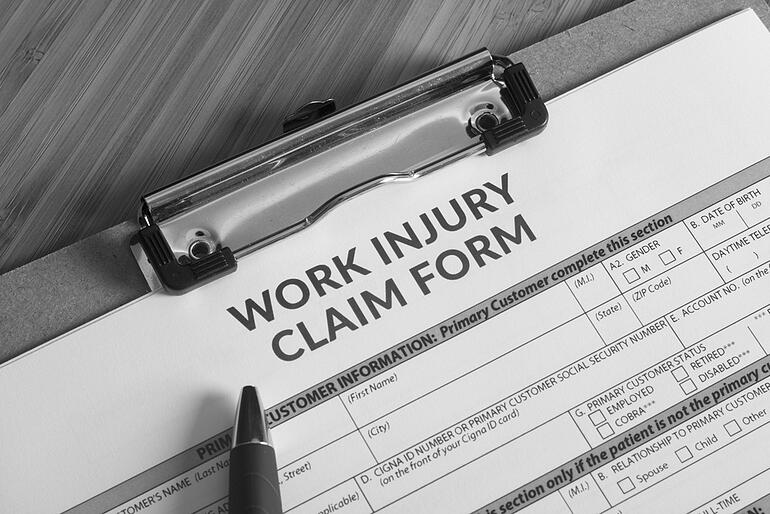 work injury claim form on desk with pen