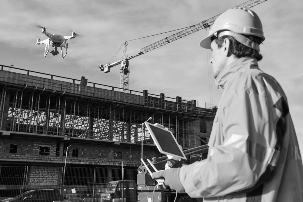 construction worker with hardhat flying a drone near a construction site