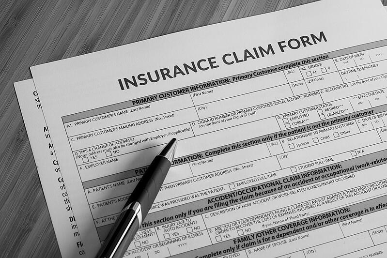 insurance claim form on desk with pen