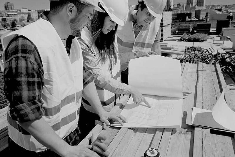 three construction workers with hard hats and uniforms reviewing documents outside of worksite