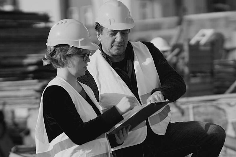 female and male construction workers reviewing worksite plans outside on a tablet