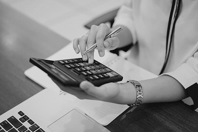 hands wearing a watch and holding calculator and pen at desk in front of notebook and laptop