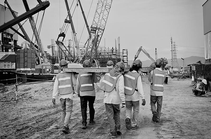 construction workers carrying steel beam through a construction jobsite