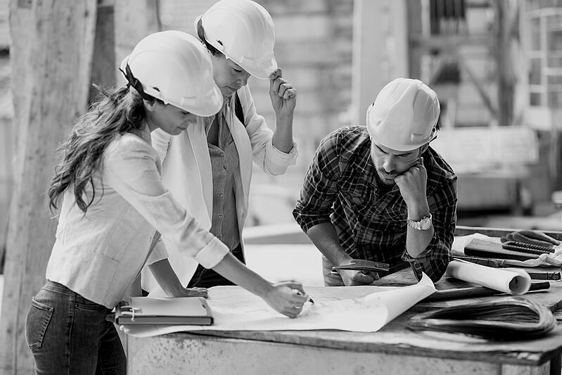 two female construction workers in hard hats reviewing design plans with male construction worker