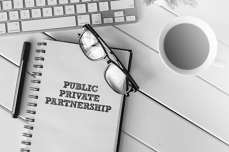 notebook with public private partnership on a desk with coffee cup, keyboard, and glasses