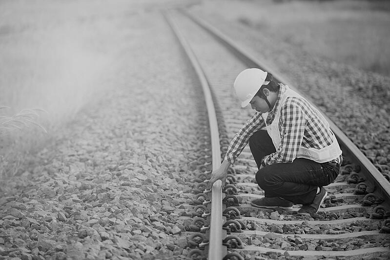 construction worker on railroad tracks observing stability of rails