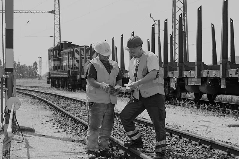 two male construction workers with hard hats at railroad tracks