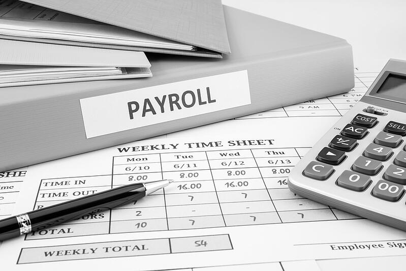 payroll binder and weekly time sheet  on desk with pen and calculator