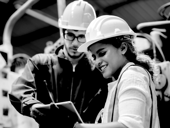 Construction woman and coworker discussing project with clipboard on project site