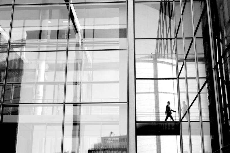 person walking in tall office building with many glass windows