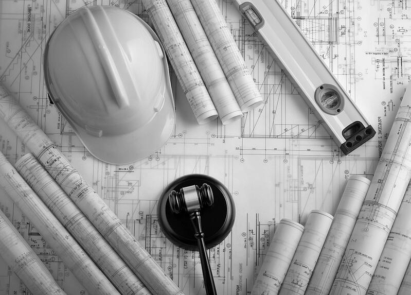 construction documents and design plans with hardhat and mallet