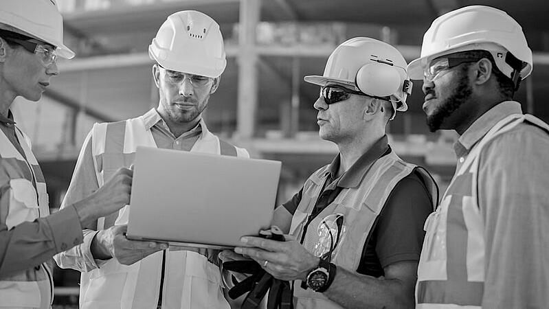 three male and one female construction workers with hardhats looking at laptop screen together at project site