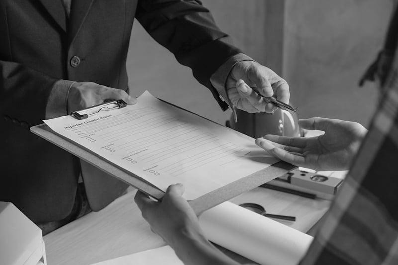 man handing insurance report and pen to worker