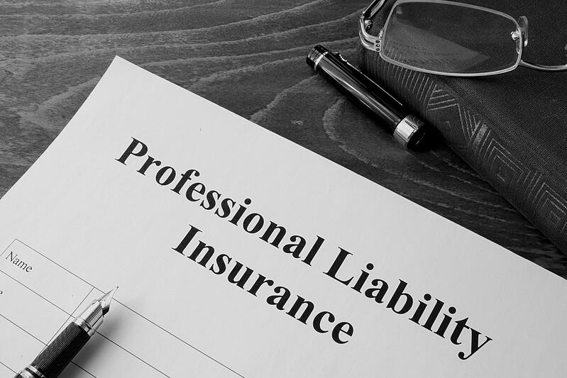 Paper document and pen with professional liability insurance