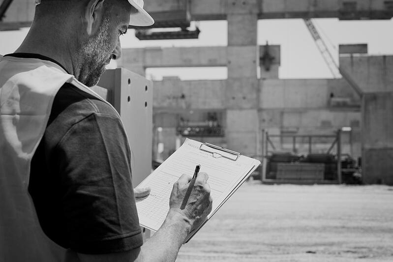 construction worker with hardhat writing on clipboard at construction worksite