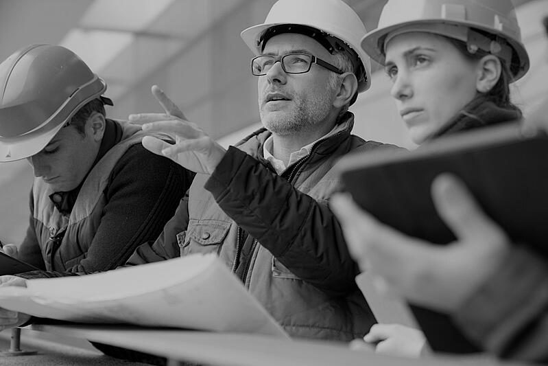 group of three construction workers analyzing jobsite