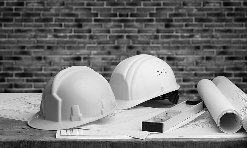 two construction hardhats and paper plans on a desk in front of brick wall