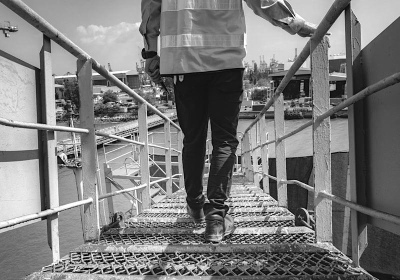 construction worker descending steel stairway to construction jobsite