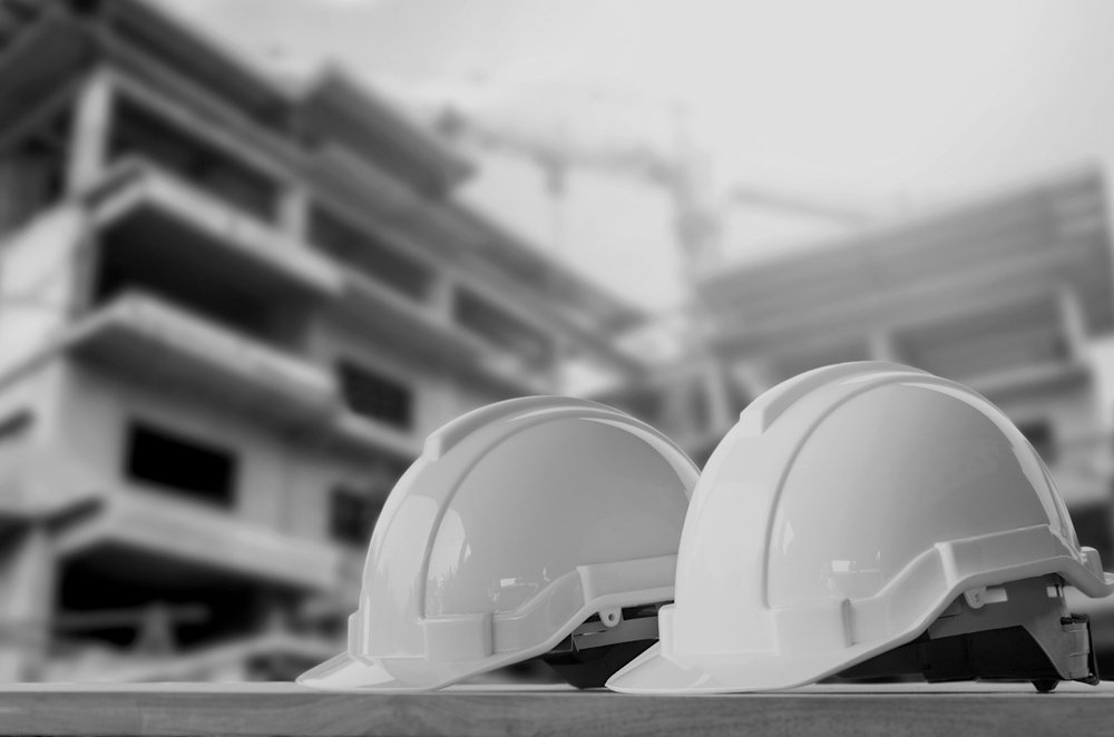 two construction hard hats outside near a worksite and building
