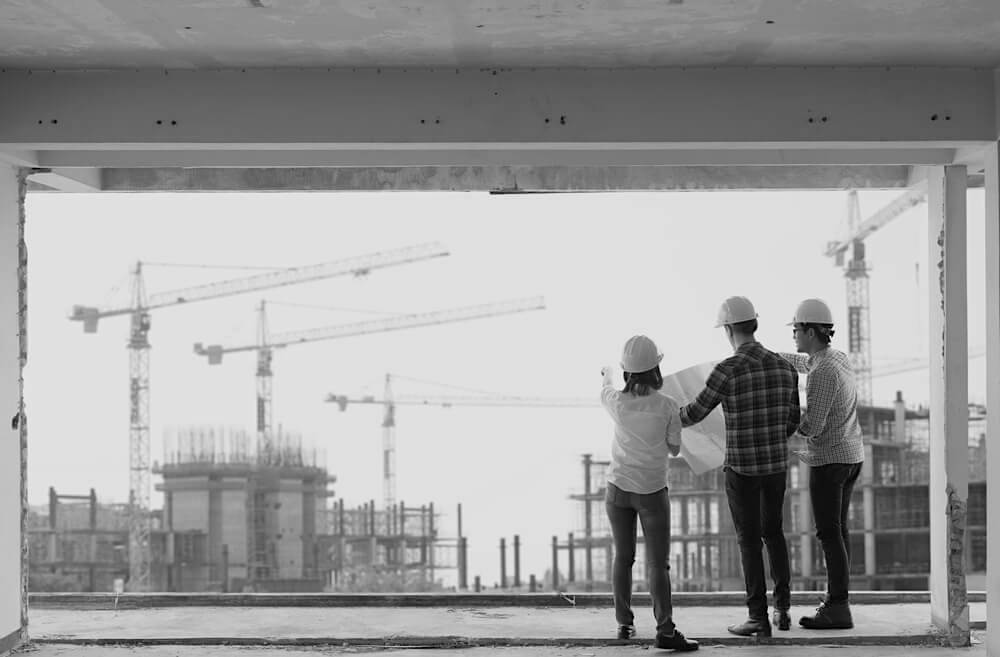 back view of three construction workers in building looking out large window at project site