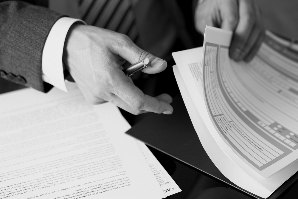 businessman hand with pen reviewing documents in a large stack of papers