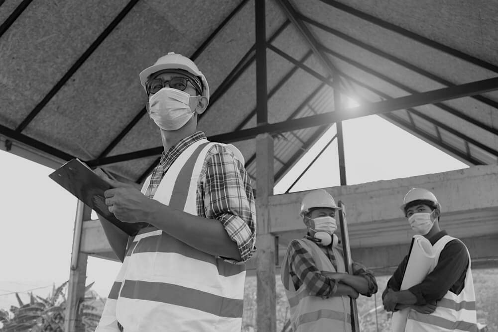 team of three construction engineers wearing masks and hardhats at a construction site under a roof