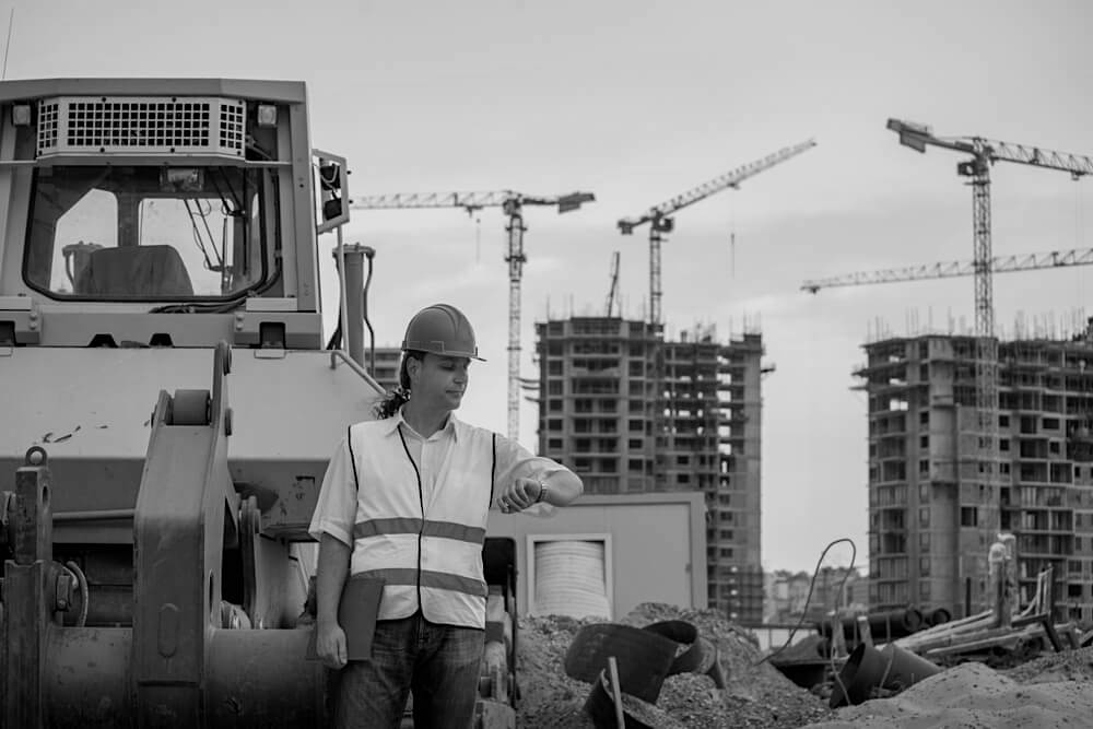 male construction worker standing by a tractor at worksite and looking at watch