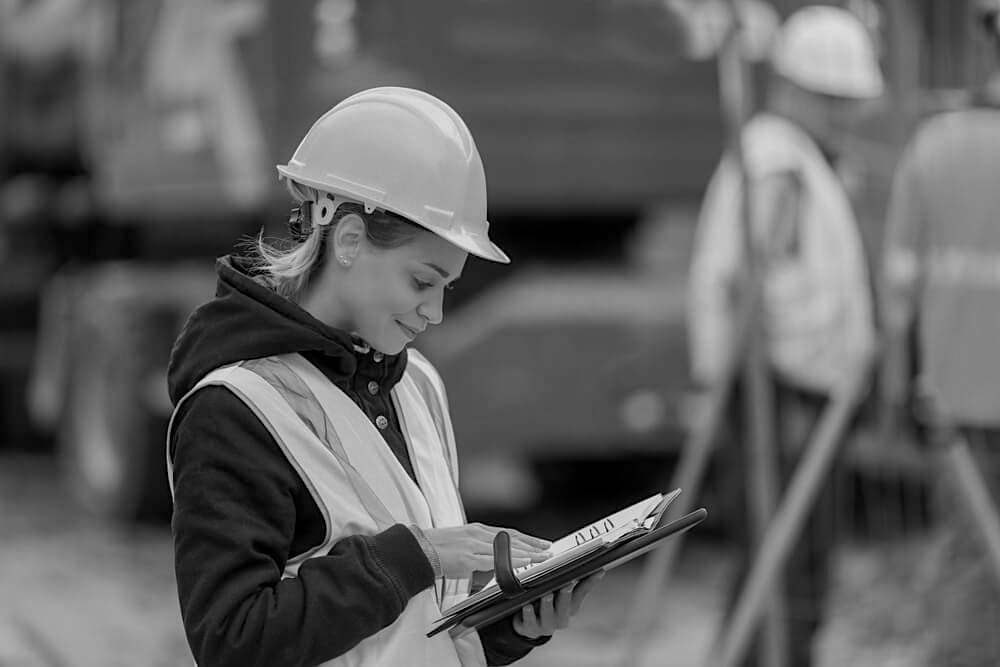 female construction worker with hardhat holding notebook outside at construction site