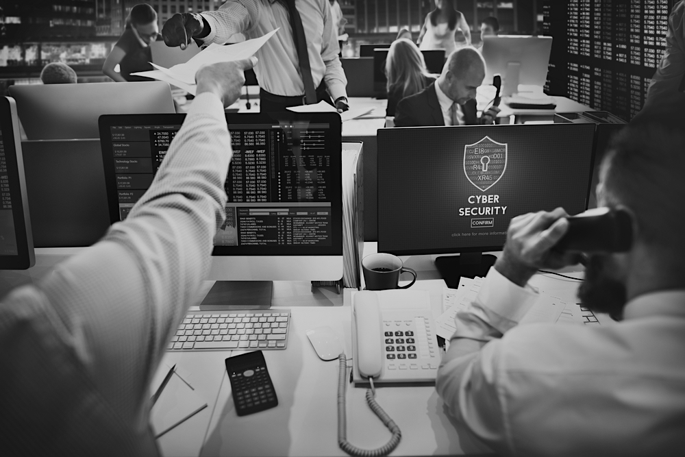 businessmen on phone in office and at a computer with cyber security threat on screen