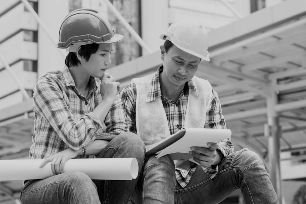female and male Asian-American construction workers with hardhats reviewing work plans at construction site
