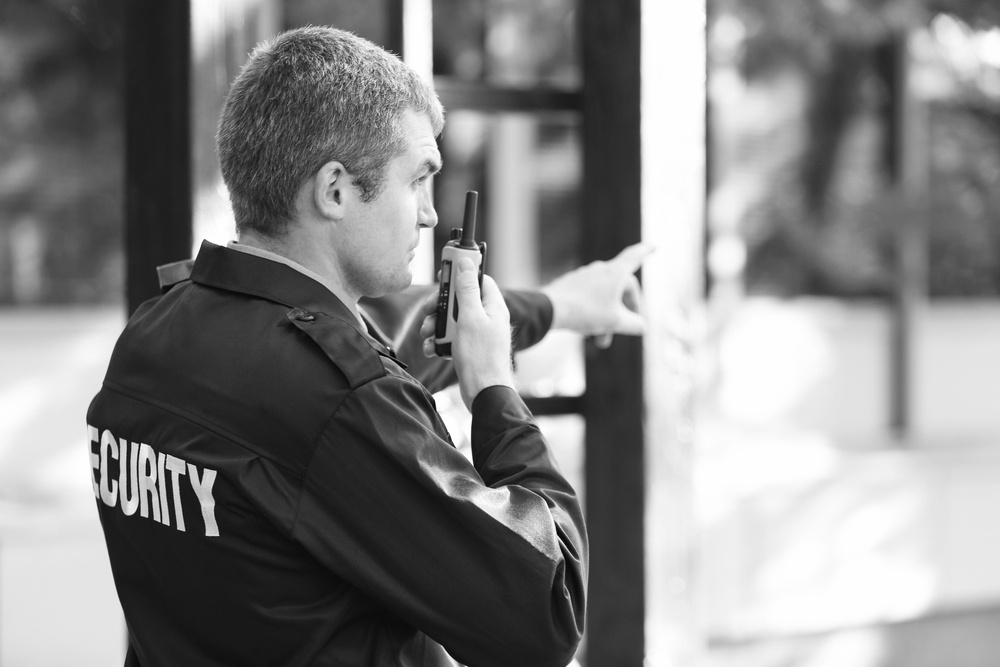 security officer in uniform holding walkie talkie and pointing